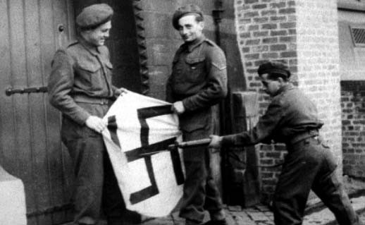 Members of the Pioneer Corps stabbing a Swastika in Brussels 1944