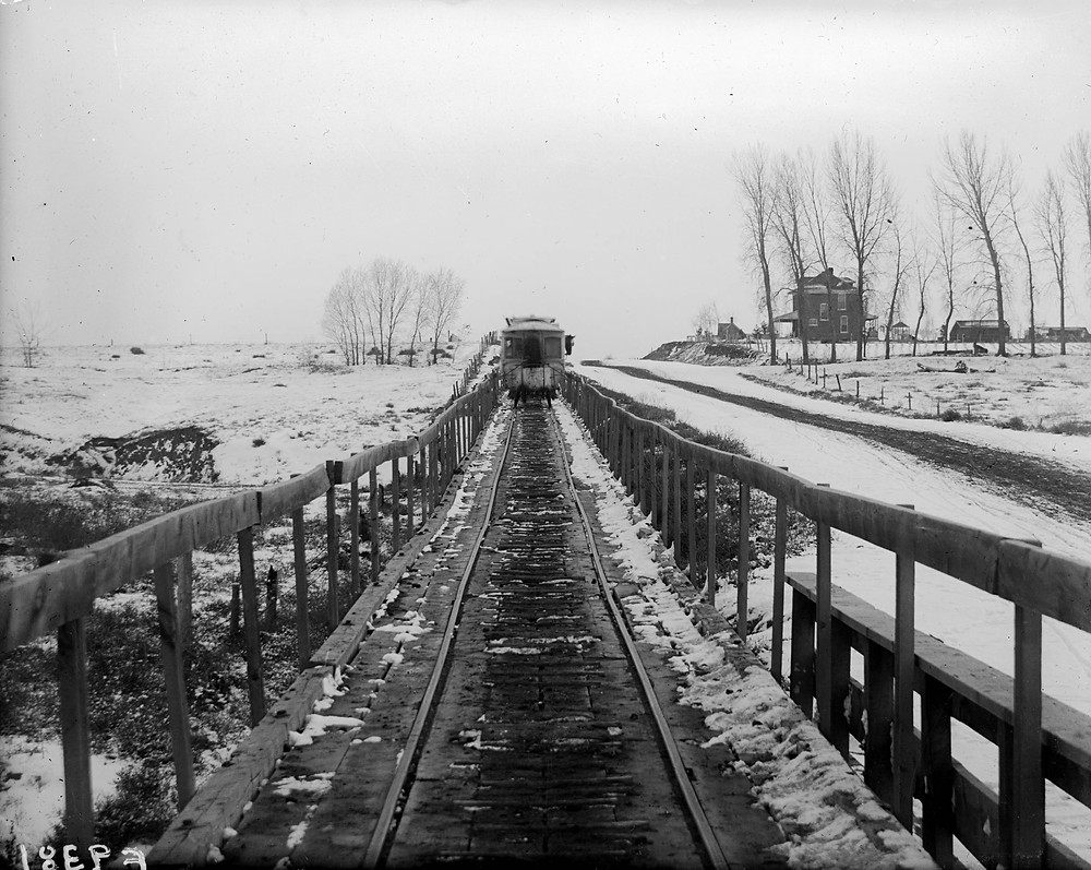 Looking south, the trolley rolling toward the trestle over Little Dry Creek. The house on the right still stands at Kenyon and Broadway.