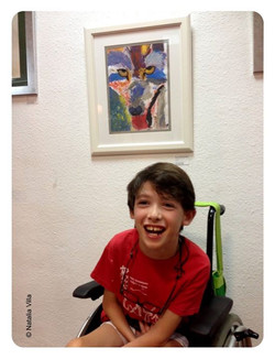 Bruno, feliz bajo su cuadro en la exposición de obras de los Talleres de Verano.jpg (Pintado con la