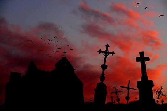 A imagem representa um cemitério com as sombras de uma capela e lápides sob nuvens vermelhas.