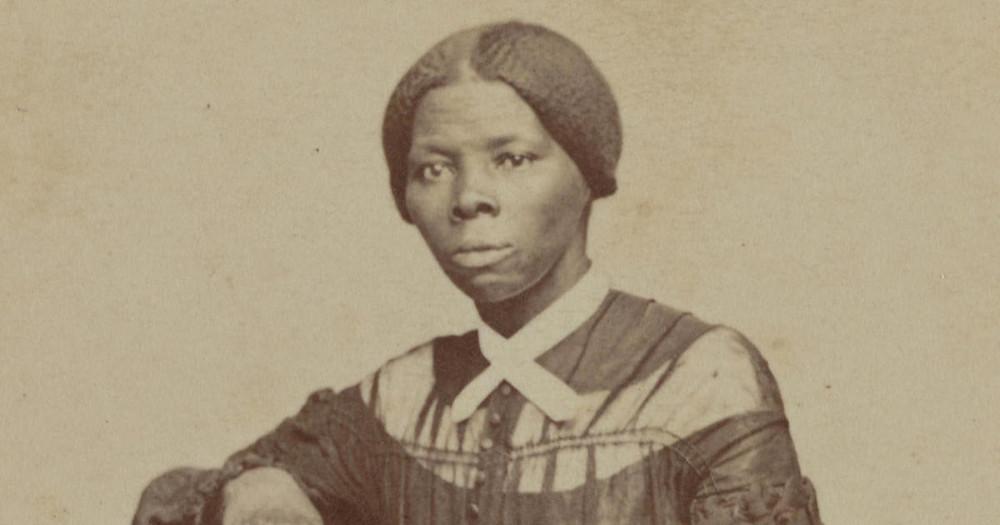 A imagem mostra uma foto amarelada de Harriet Tubman, uma mulher negra, com cabelos presos e roupas fechadas. Ela encara a câmera sem sorrir.