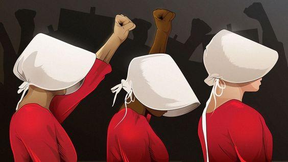 A imagem mostra três mulheres vestidas de aia, com vestes vermelhas e capuzes de aba frontal brancos, erguendo os punhos em protesto.