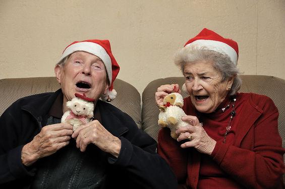 Old senior couple with santa hats celebr