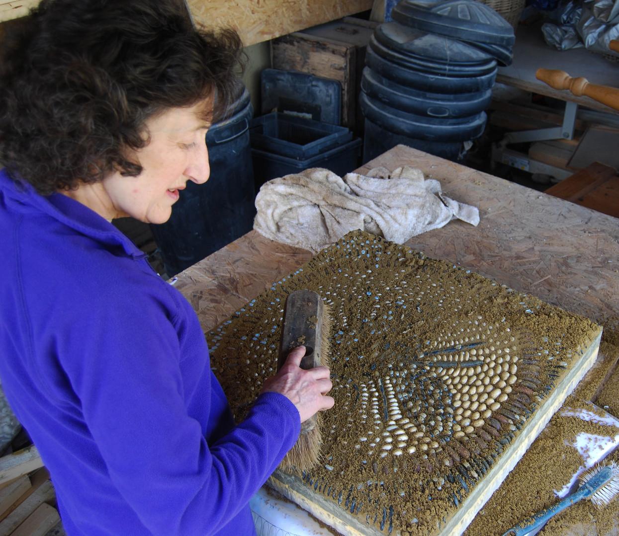 Sue Rew brushing down mosaic