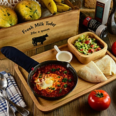 Shakshuka - Served in a hot pan with side dish and Pita bread