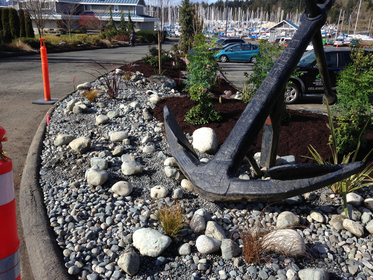 Large anchor sitting in a drystream of river rock and plants at the Westport Marina