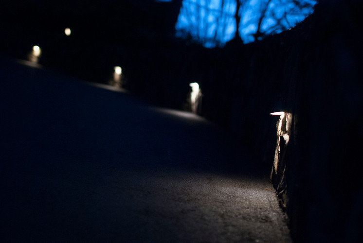 Landscape lights on rock wall cascading light on driveway