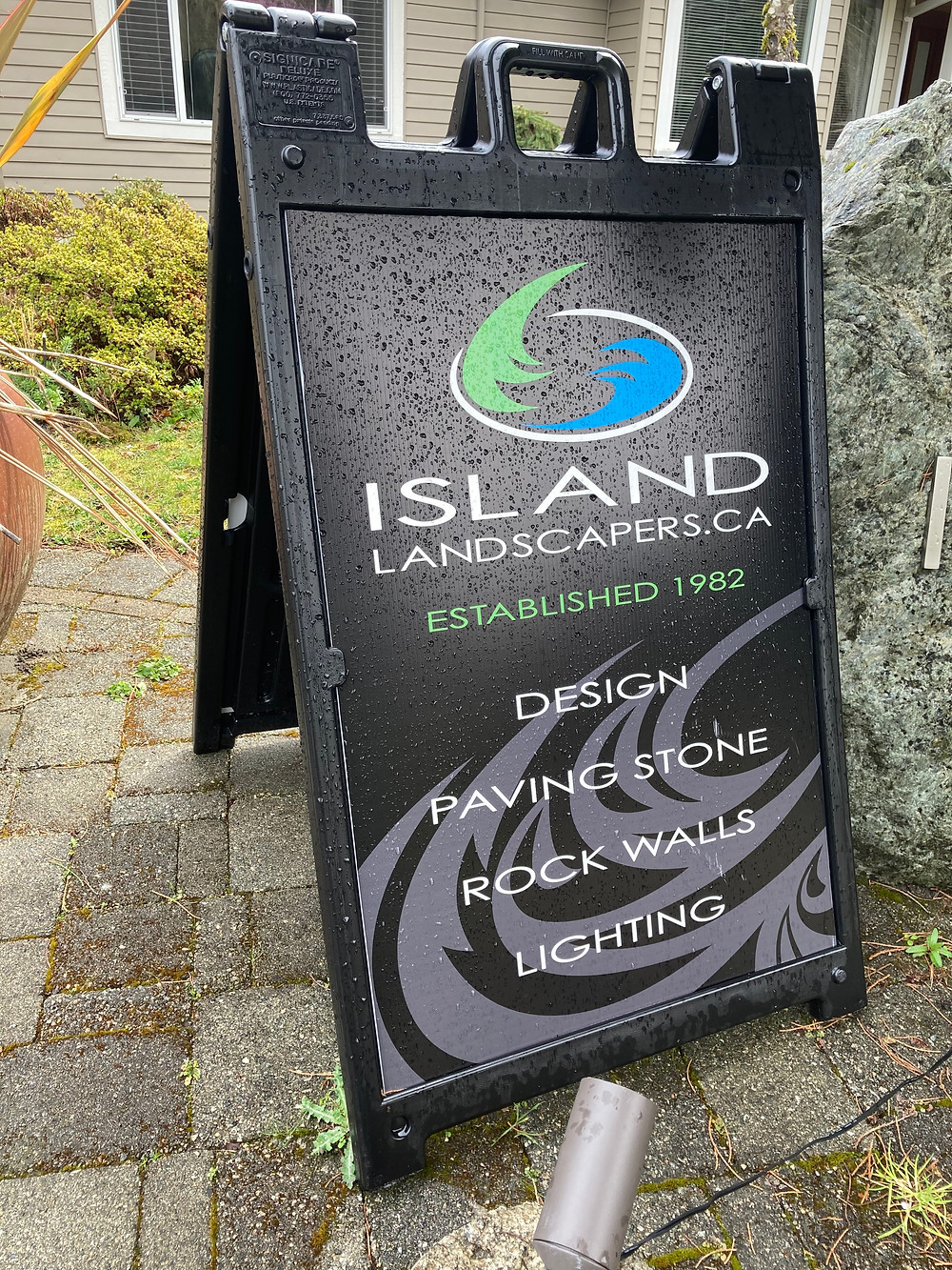 Island Landscapers Inc. sign in black featuring design, paving stone and rock walls.