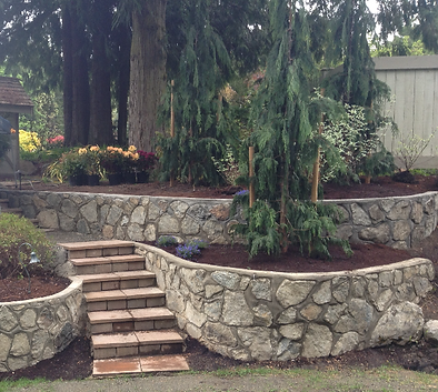 Terraced garden featuring masonry rock walls and curved stairs.