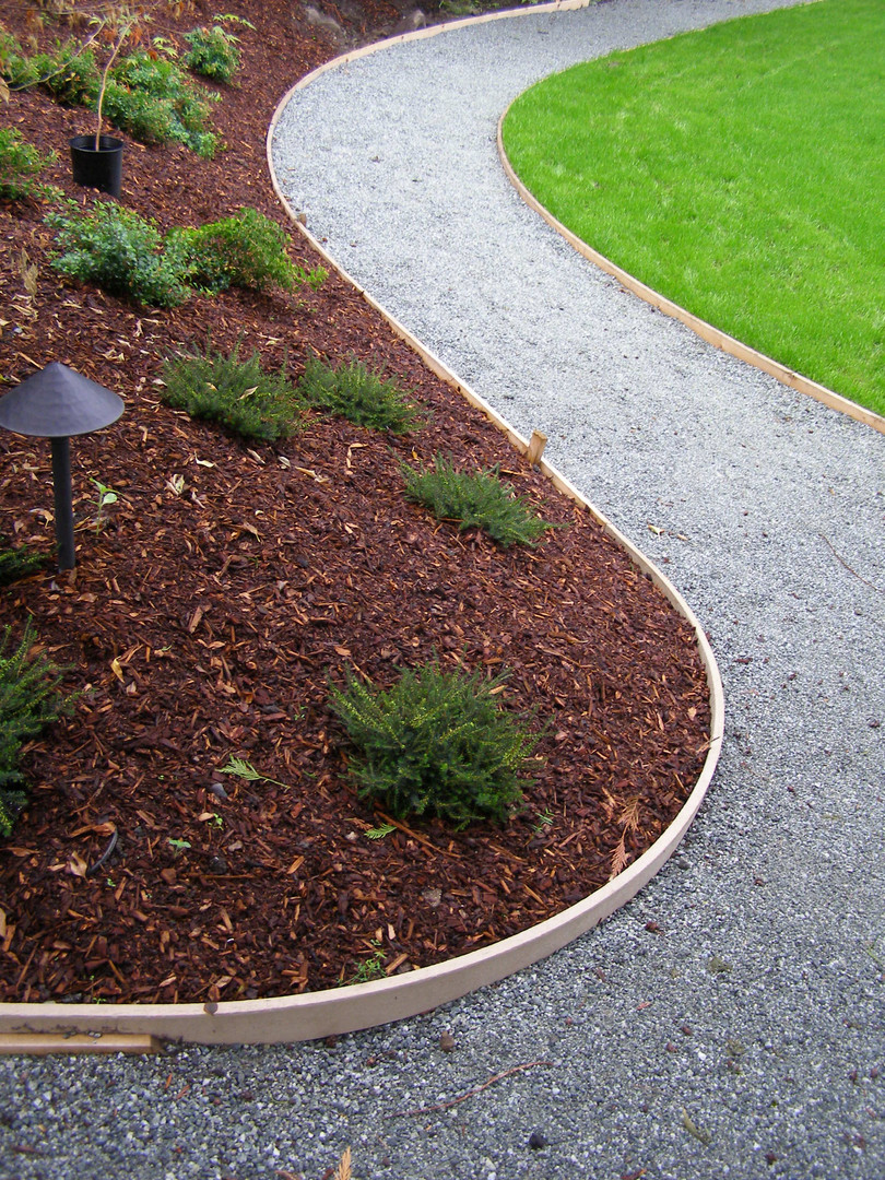 Landscape light in raised shaped garden beds with path and lawn