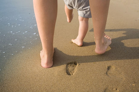 Mother and child walking on a sandy beac