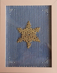 Filet mesh background using fine crochet thread. Snowflake crocheted separately and sewn onto mesh, along with a few beads