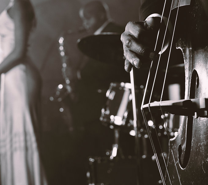 Man Plucking a Double Bass  in a Nightclub and a Female SingerStanding