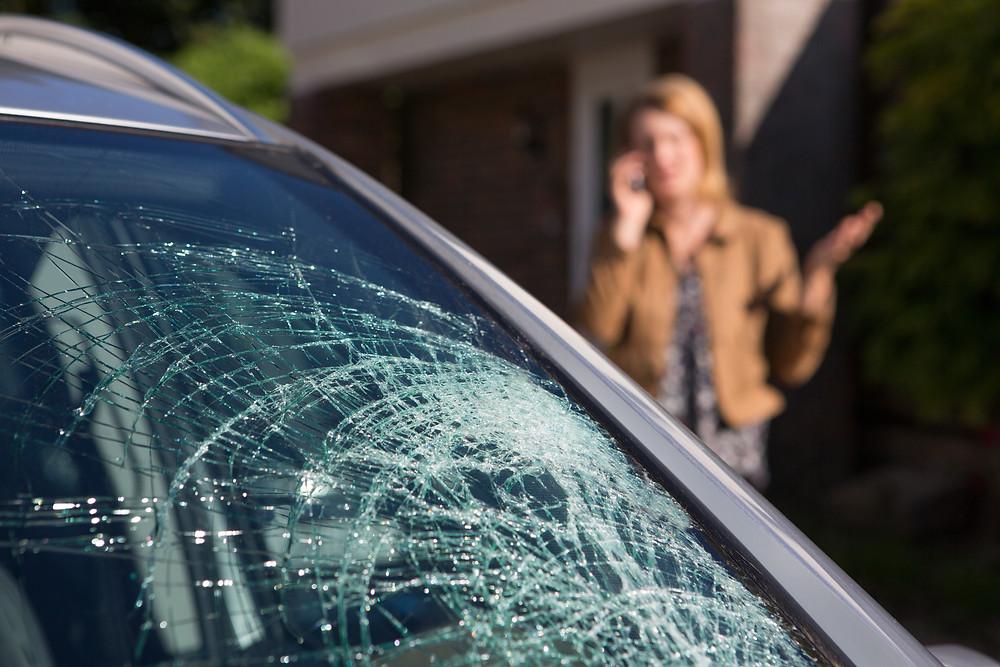 Woman Inspects Windshield Damage