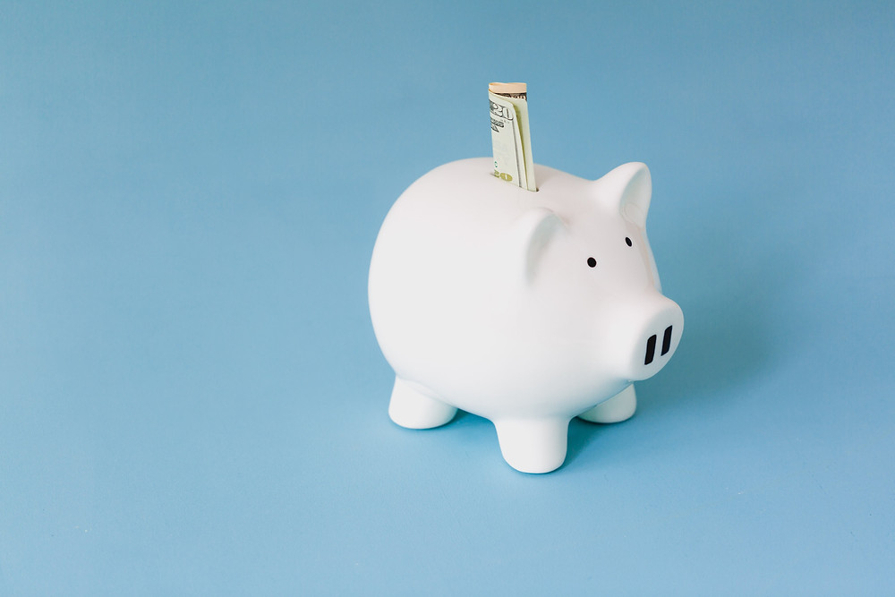 Piggy bank with money halfway pushed in