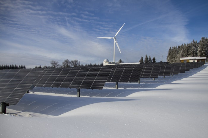 ground mounted solar panels with windmill in background