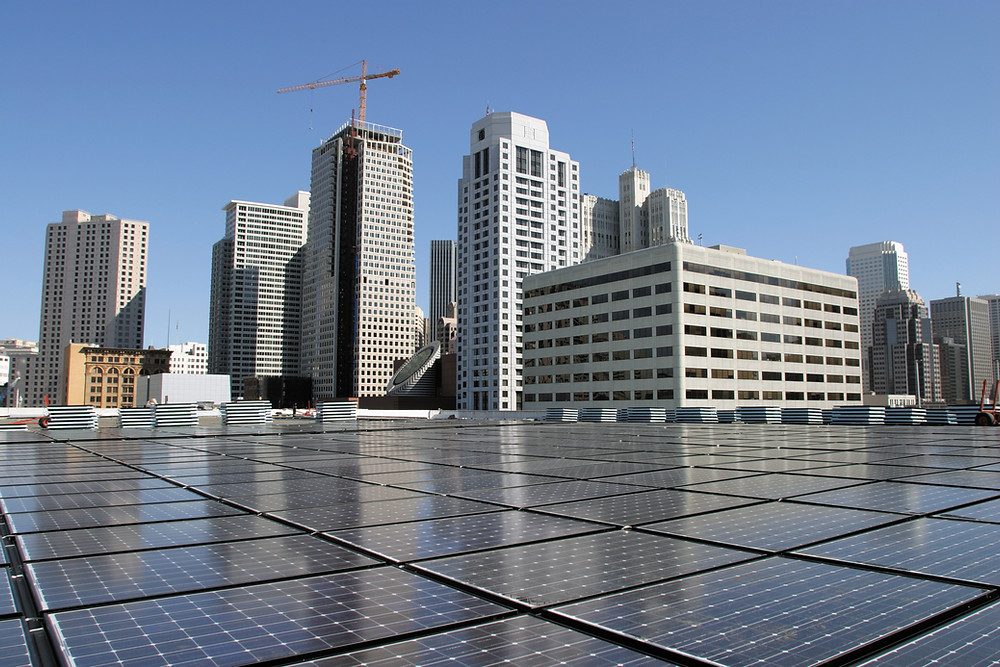 commercial solar panel array with skyscrapers in the background