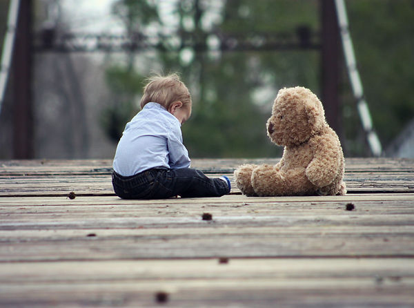 A young child sitting close to his favourite bear