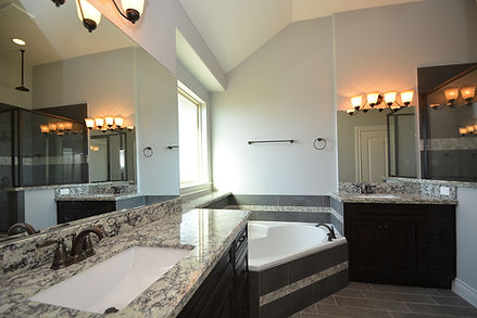 master bathroom with granite counters gray tile antique bronze fixtures