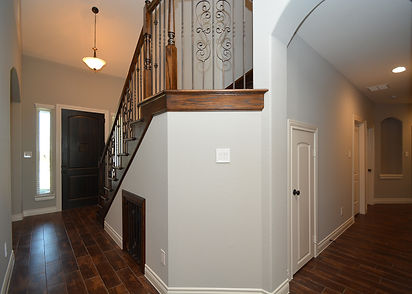 Lipka custom home Greater Houston view of front door entrance stairs with wrought iron railing and hall to bedrooms