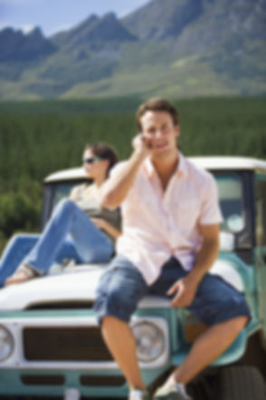 Young couple sitting on bonnet of parked