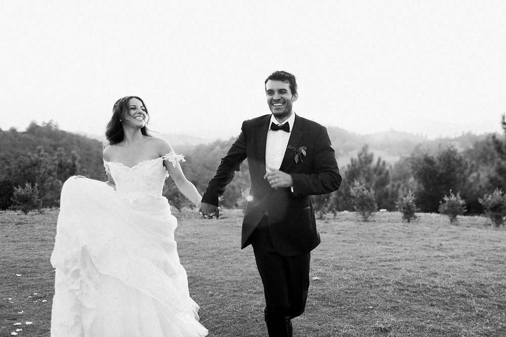Black and White photo of Bride and Groom running together at Sunset.