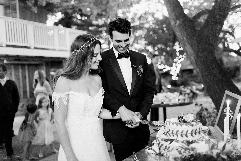 Black and White photo of Bride and Groom cutting cake together.