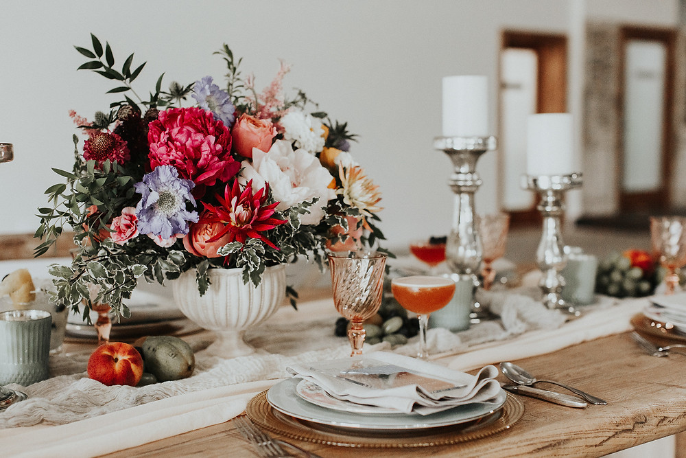 Dining table with punchy florals, organic produce, and custom cocktail