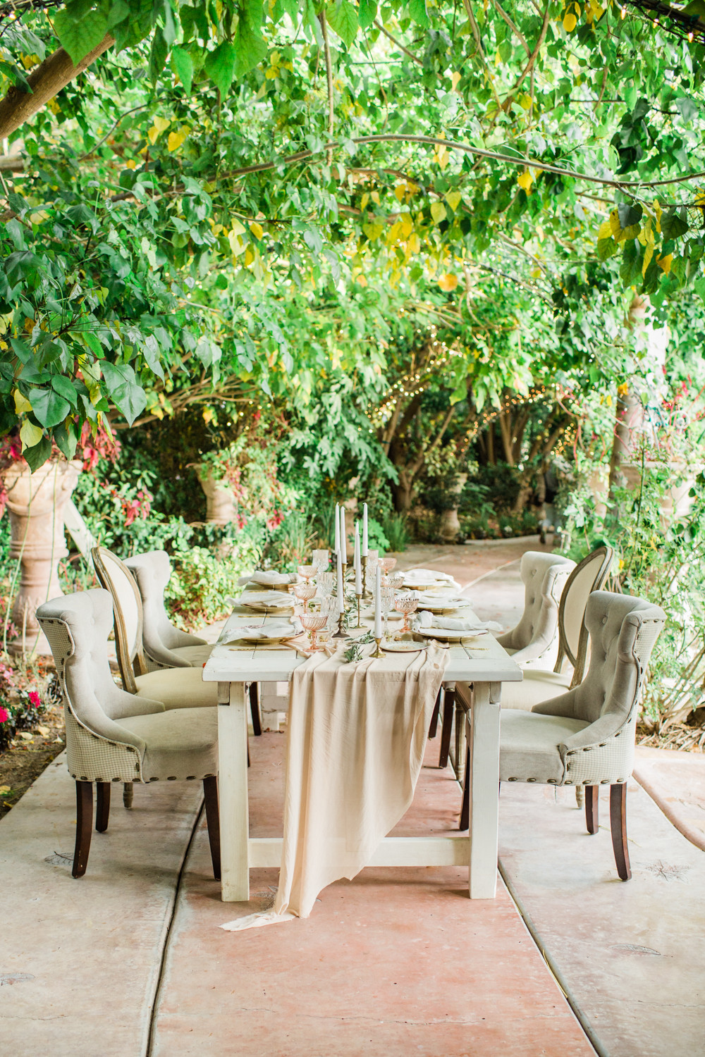 Dining table set under a canopy of trees