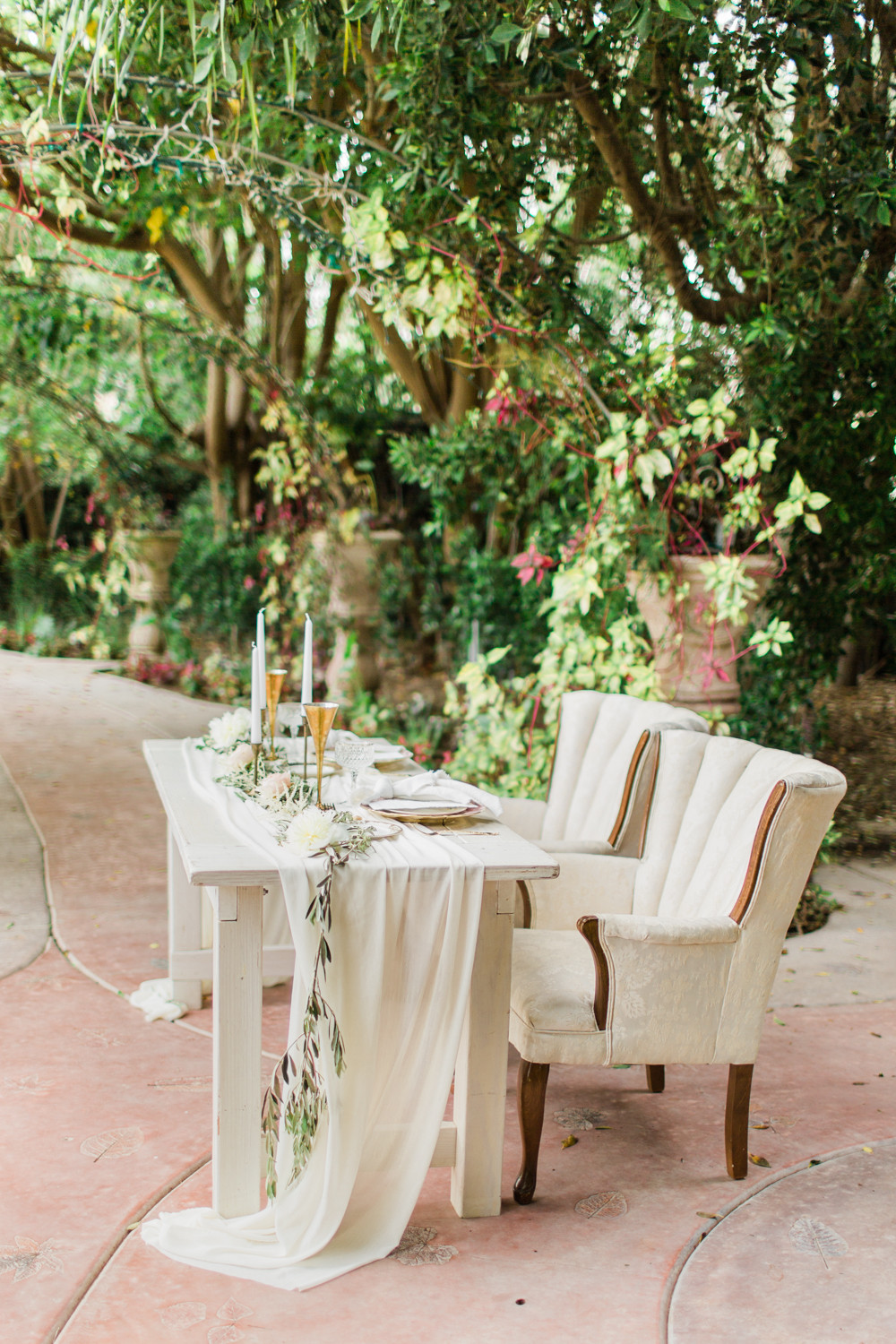 Sweetheart table set under a canopy of trees