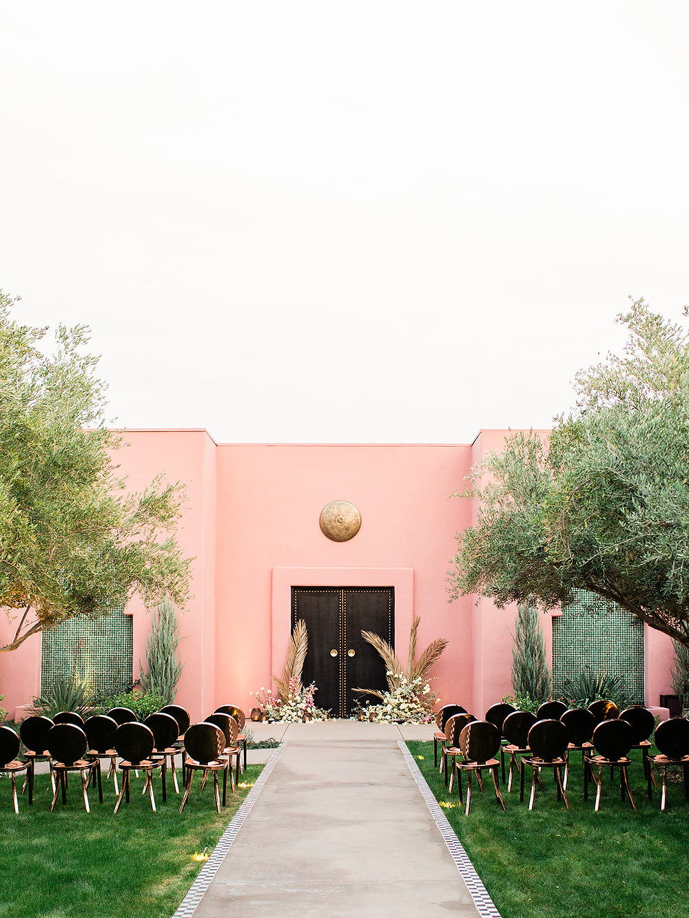 Modern Moroccan Desert Glam Editorial - LGBTQ Wedding Editoiral - Wedding Design Inspiration - Muted Desert Tones - Modern Glam Jungle Chic Modern ceremony space with copper chairs and pink wall