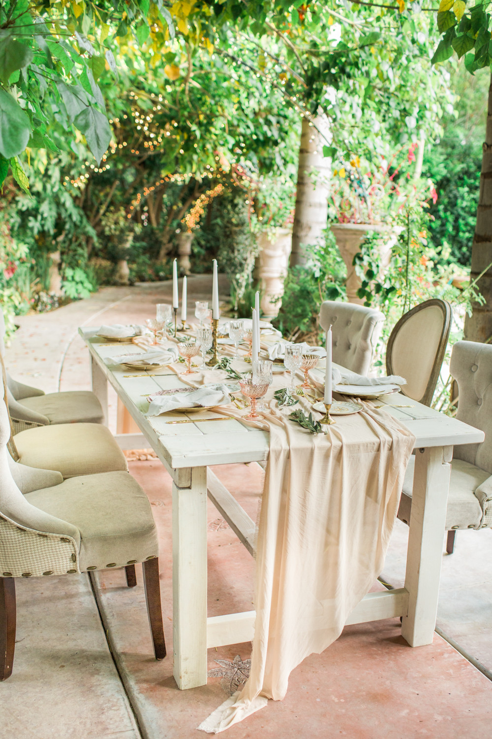 Dining table under a tree grove with mis-matched seating