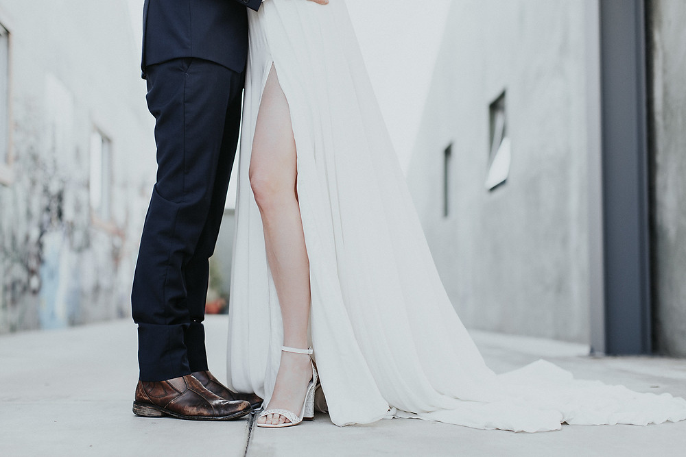 Detail of Bride and Grooms shoes. Bride shows some leg through the slit in her dress.