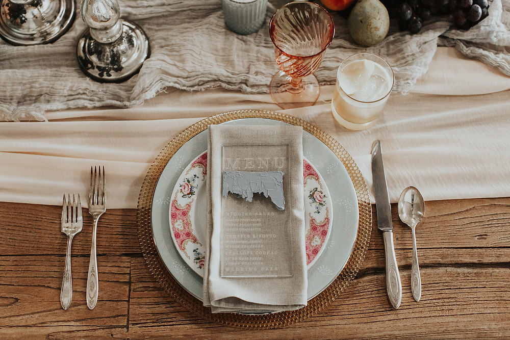 Custom place setting with lucite menu, hand dyed table runner, and floral china