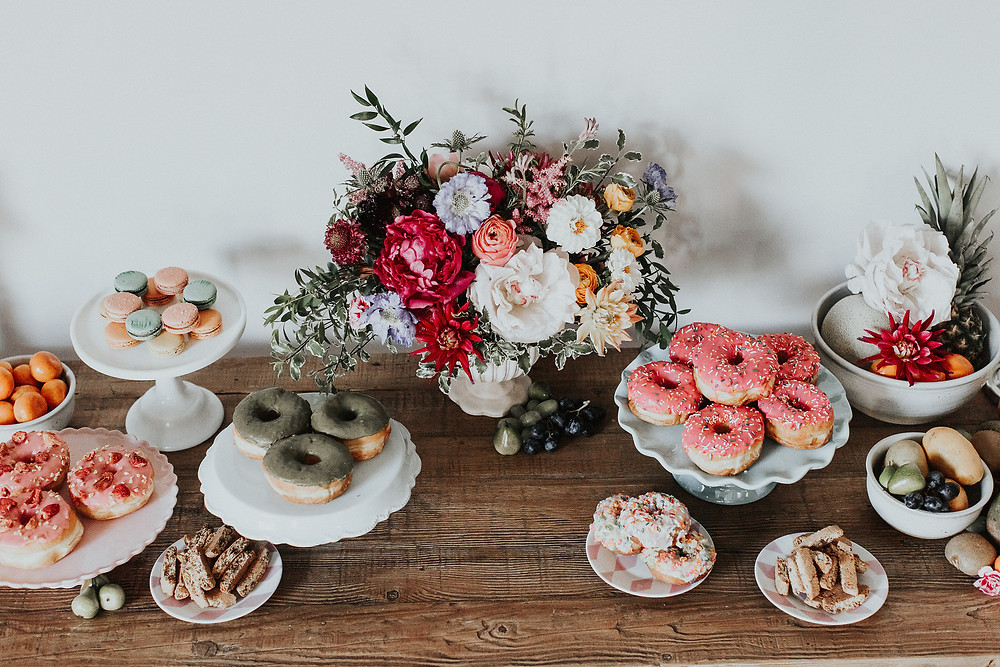 Dessert table with piles of donuts and macaroons instead of cake