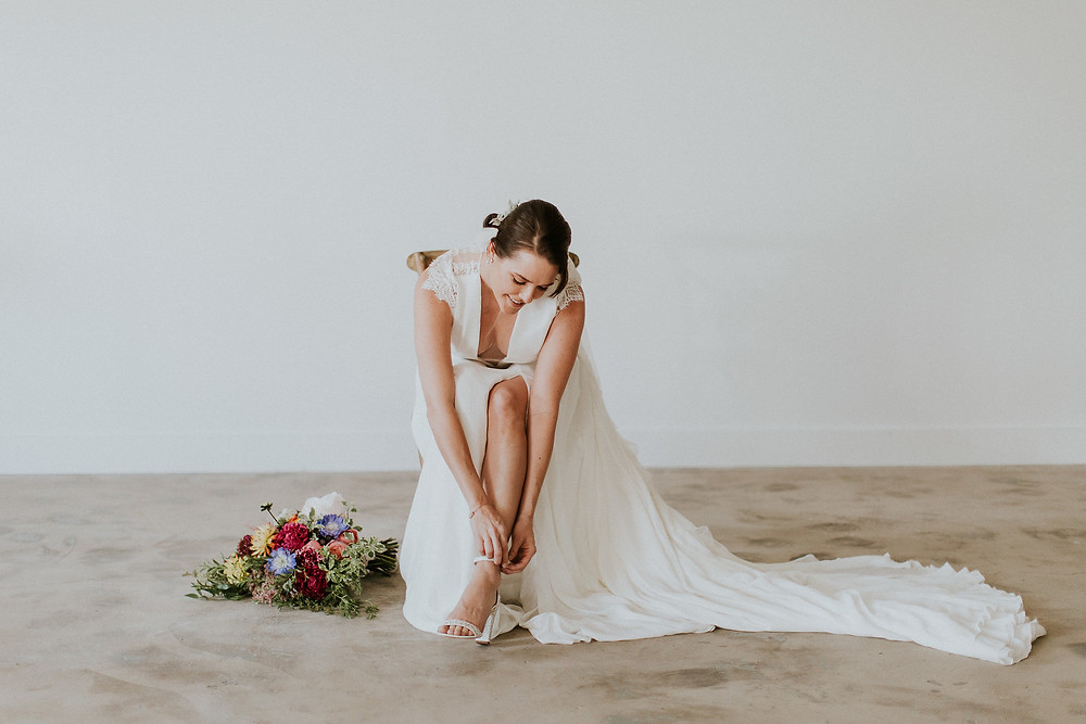 Bride shows some leg as she straps on her heels