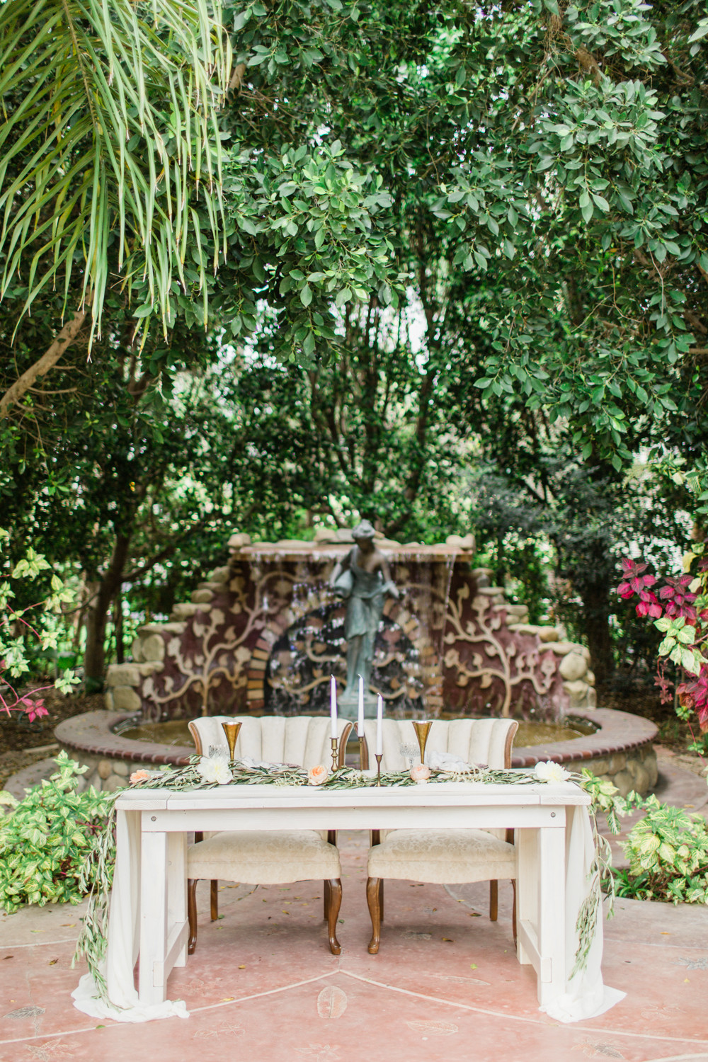 sweetheart table set in front of a stone fountain