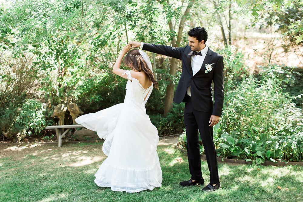 Grooms twirls his bride in the garden.