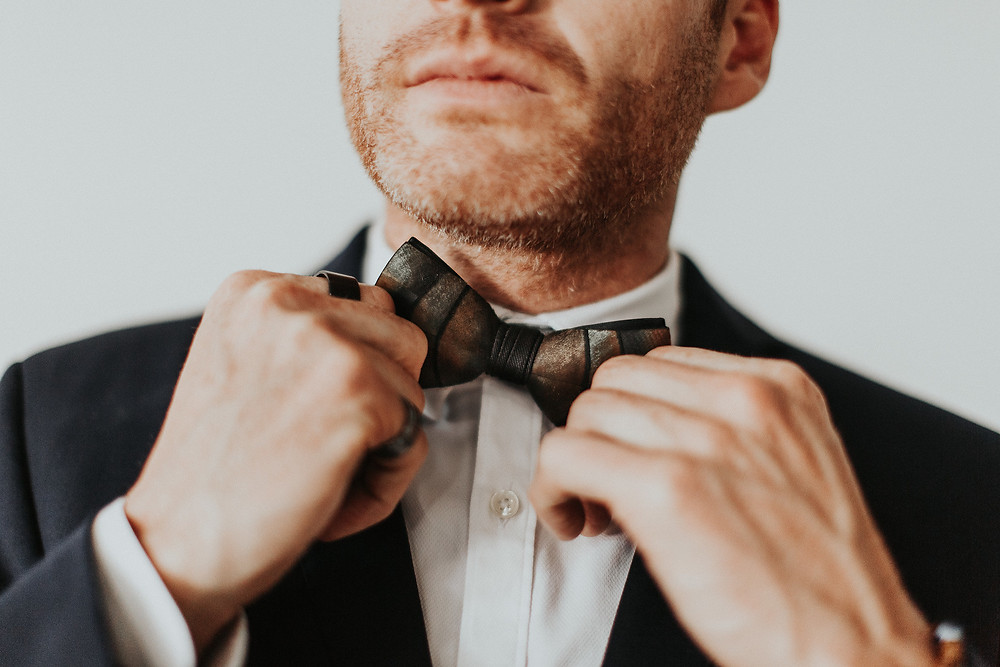 Groom straightens his bow-tie as he gets ready