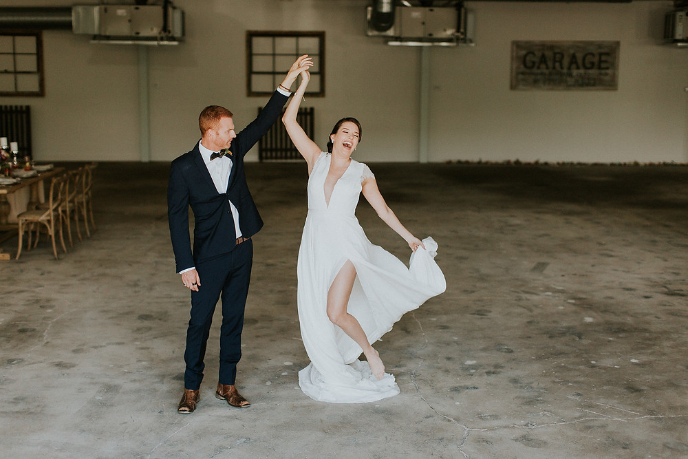 Groom twirls his bride across the industrial reception area