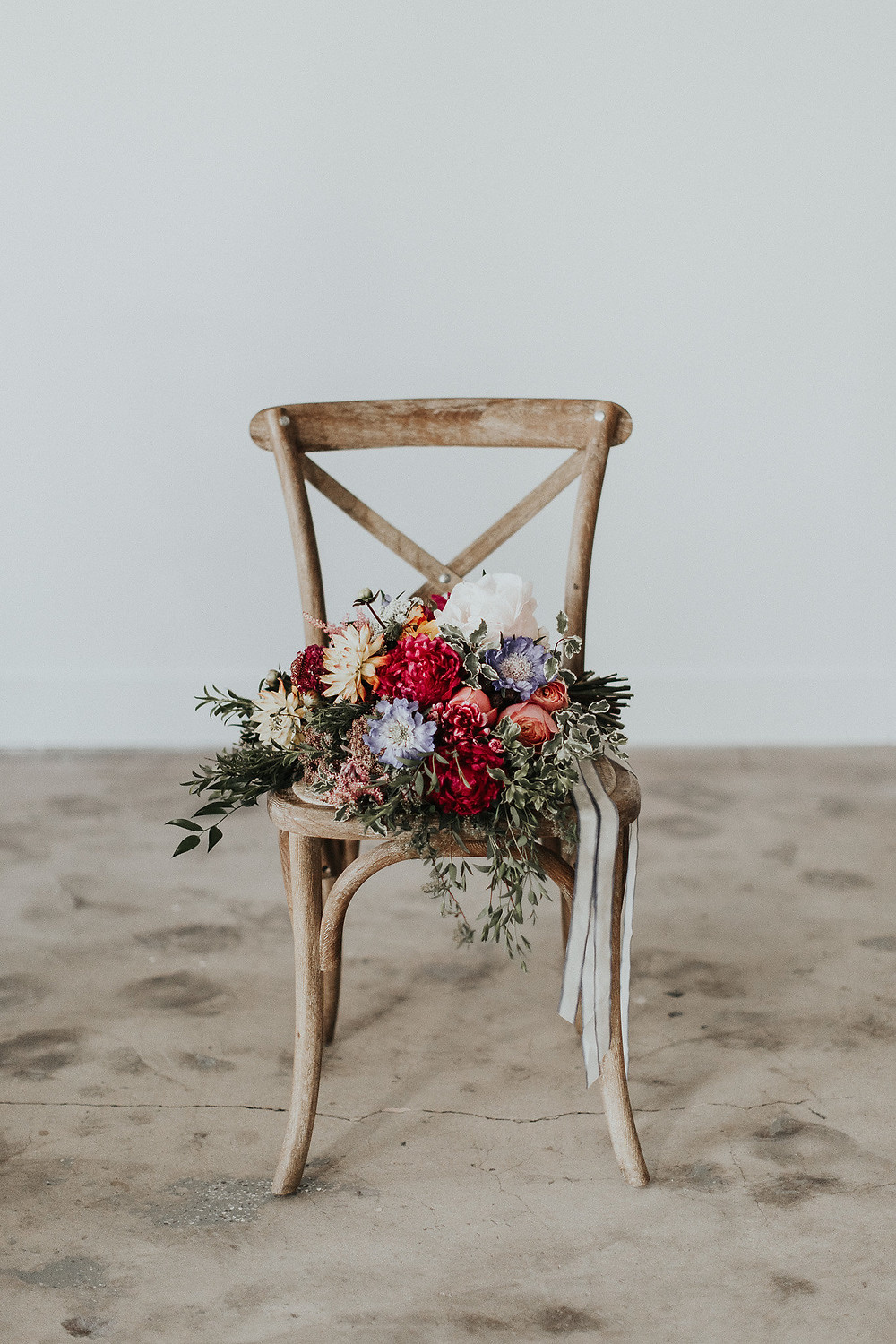 Gorgeous bridal bouquet sitting on a rustic cross-back chair
