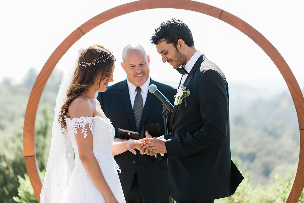 Bride and Groom exchange rings during ceremony.