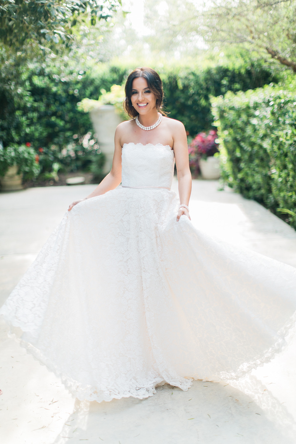 Bride poses in her dress with a big smile on her face