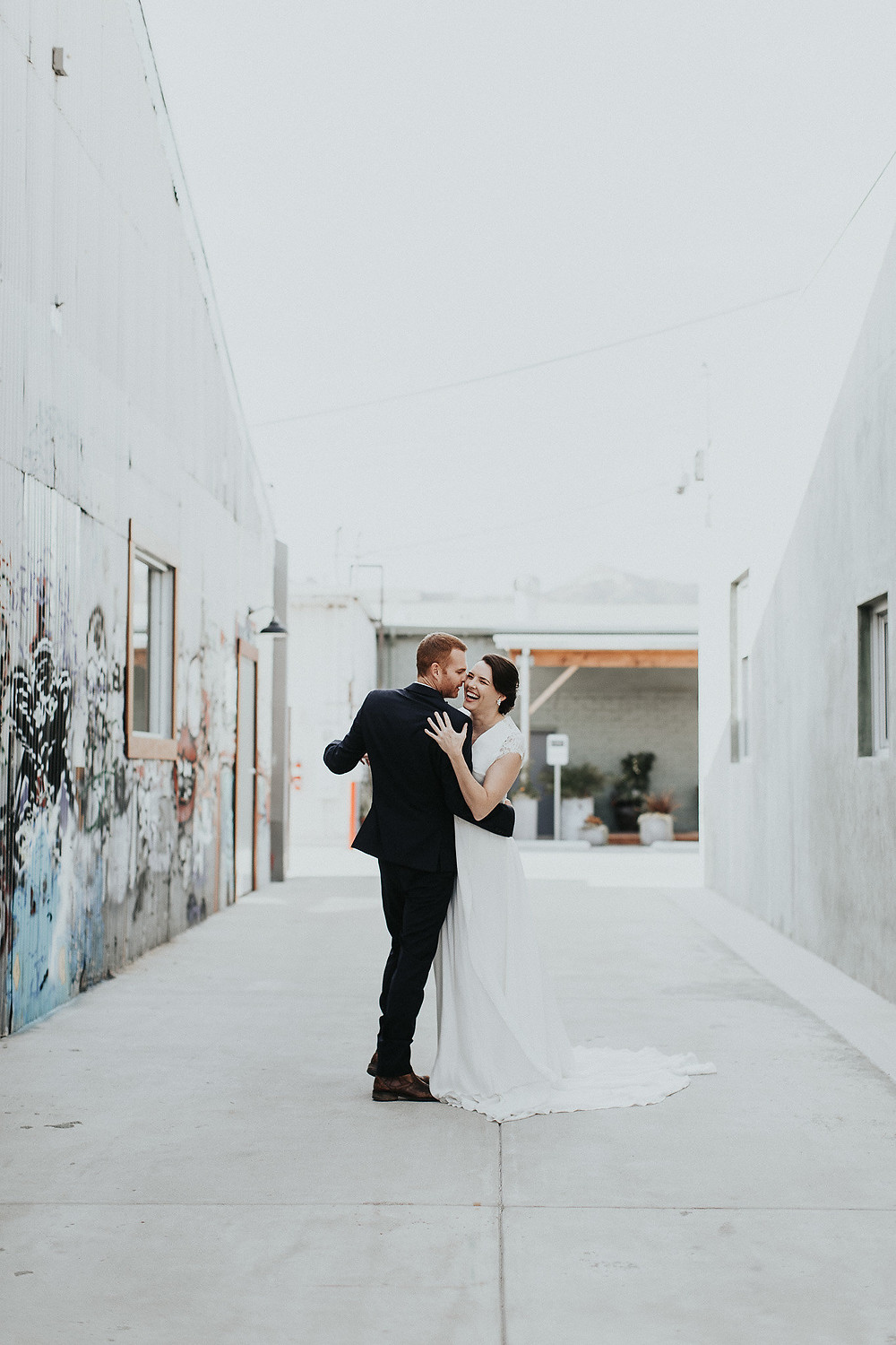 Bride and Groom laugh and twirl through the graffiti alleyways