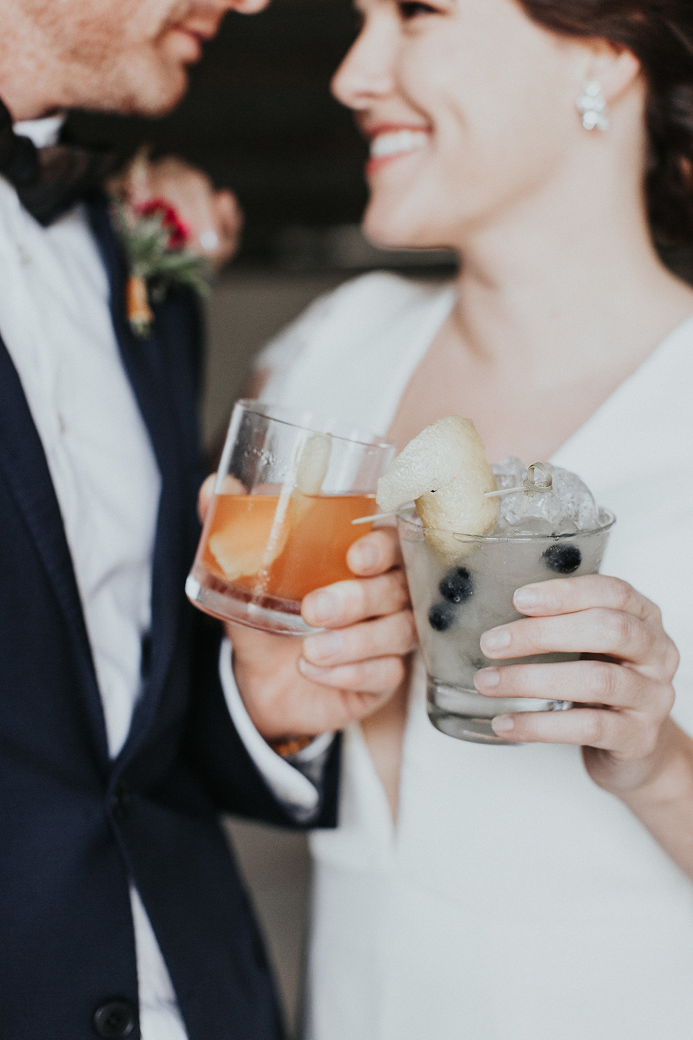 Bride and Groom smile at each other as they clink their signature drinks together