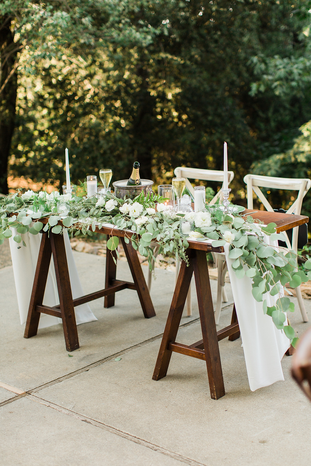 Sweetheart table with crystal candlesticks and dripping greenery.