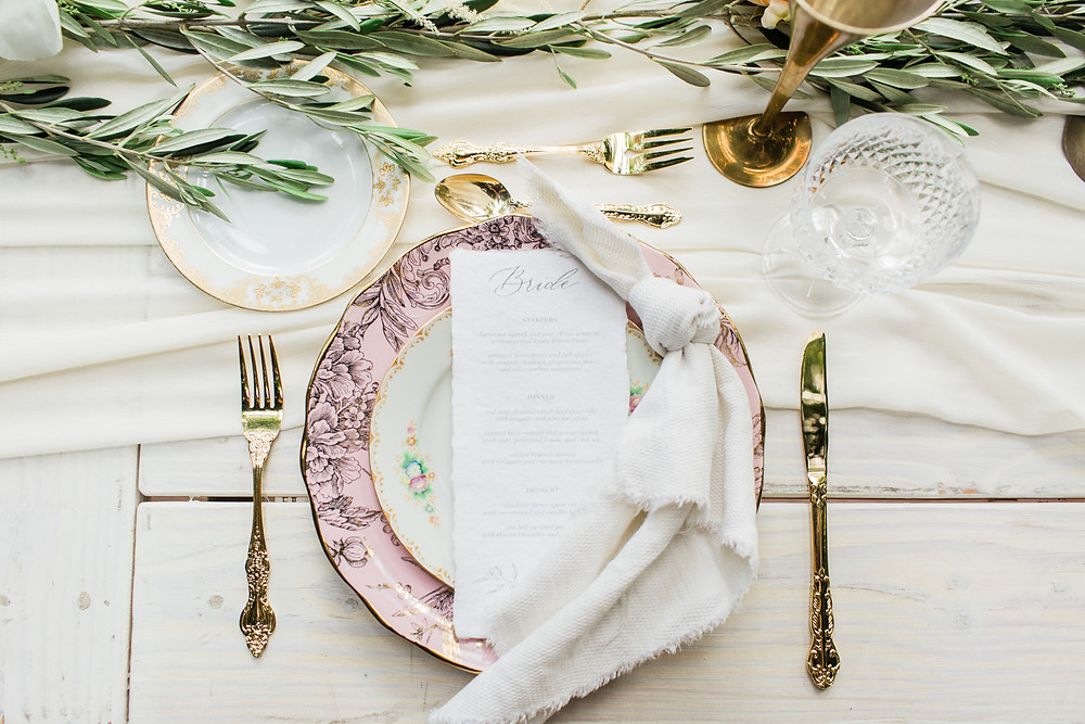 Place setting at dining table featuring mis-matched china and gold flatware
