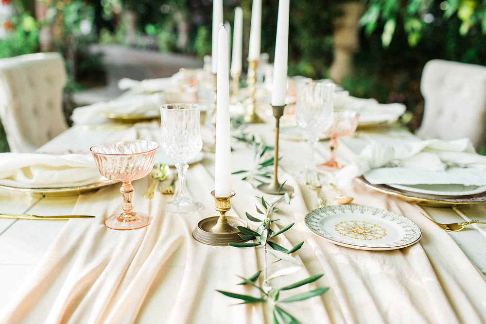 Table top design details for dining table featuring white candles and vintage brass candlesticks