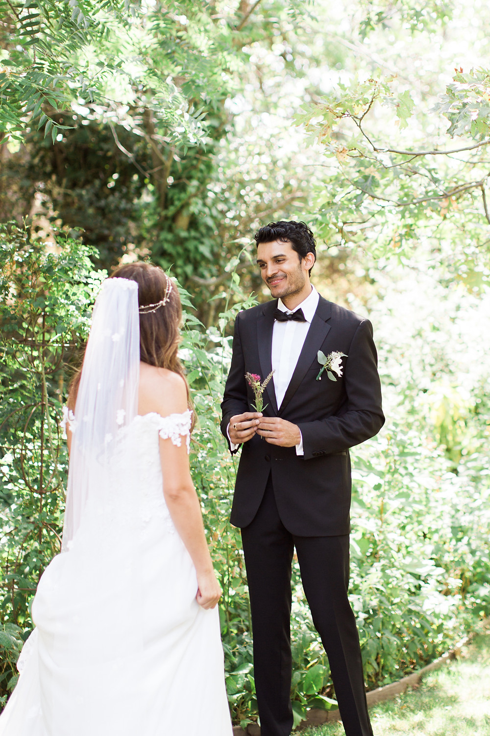 Groom smiles as he hands bride the flowers he picked for her.