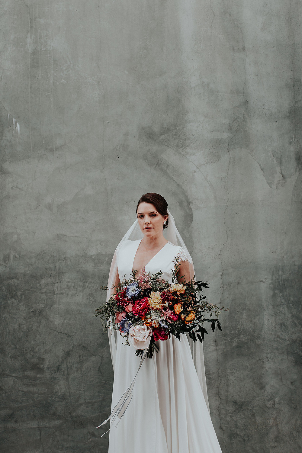Bride gives us a moody pose as she stands with her bridal bouquet against a cement wall